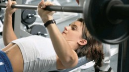 female performing flat barbell bench press