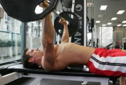 male performing flat straight bar bench press