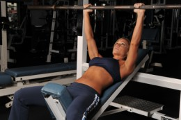 female performing incline straight bar bench press
